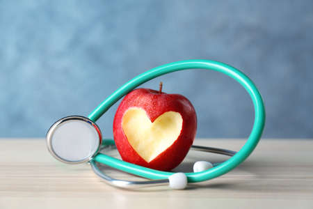 Apple with stethoscope on color background