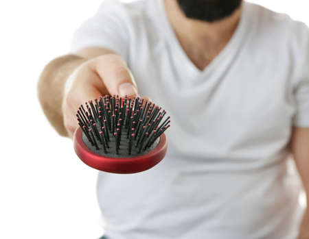 Adult man with hair brush on white background, closeup