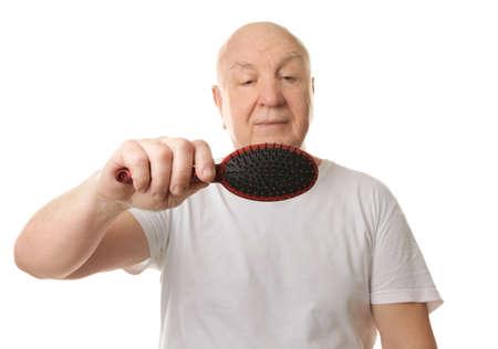Bald senior man with hair brush on white background