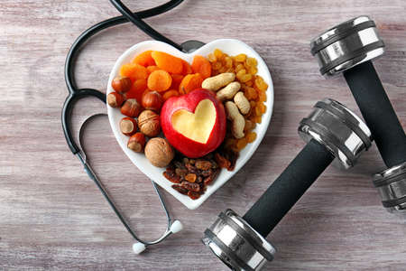 Healthy food, stethoscope and dumbbells on wooden background