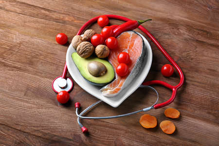 Healthy food in heart shaped plate and stethoscope on wooden background Stock Photo