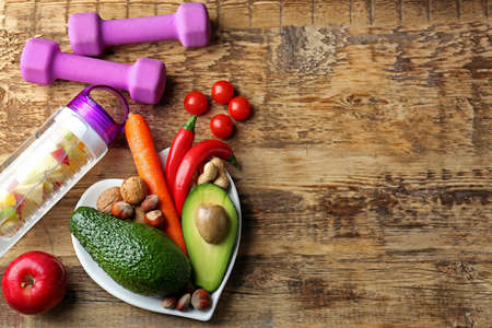 Healthy food with dumbbells on wooden background