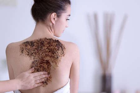 Beautiful young woman undergoing scrub treatment in spa salon