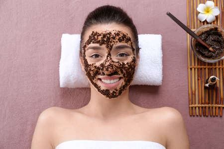 Beautiful young woman with scrub mask in spa salon