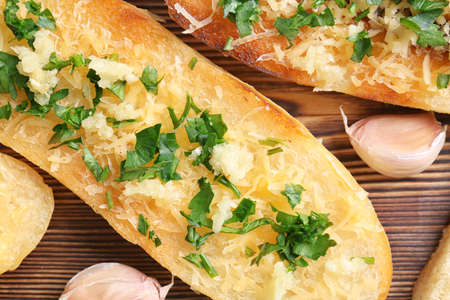 Tasty bread slice with garlic, cheese and herbs on wooden background, closeup