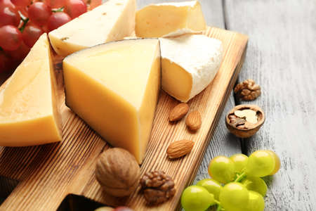 Delicious cheese, grape and nuts on wooden board Standard-Bild