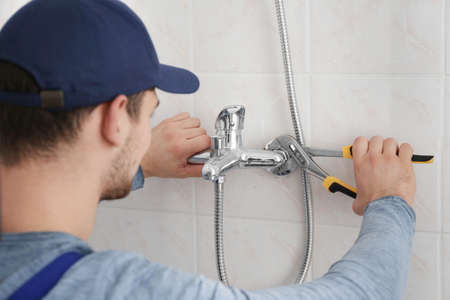 Plumber fixing faucet in bathroom