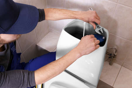 Plumber repairing toilet cistern at water closet Standard-Bild