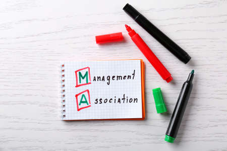 Management concept. Notepad and felt pens on white wooden table