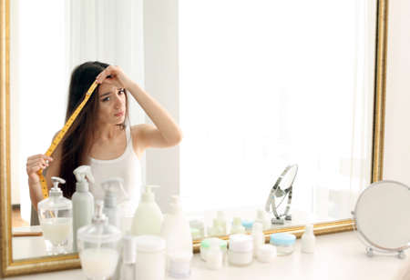 Young woman measuring hair length in front of mirror at home Foto de archivo
