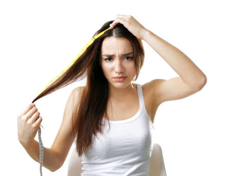 Young woman measuring hair length on white background