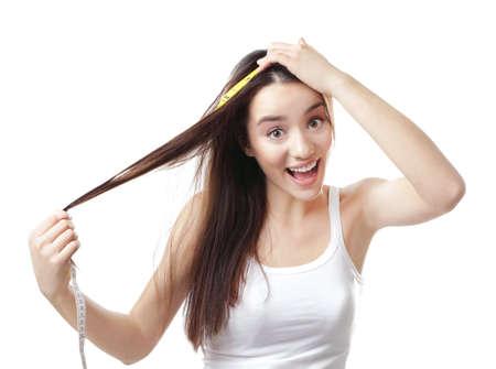 Mujer joven midiendo la longitud del cabello sobre fondo blanco Foto de archivo