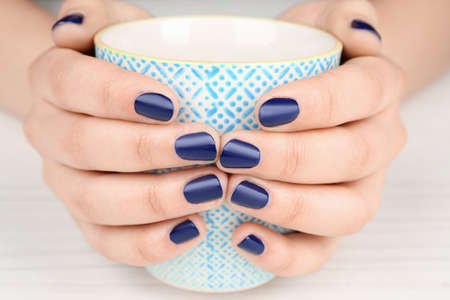 Nail art concept. Beautiful female hands with neat manicure holding cup, closeup
