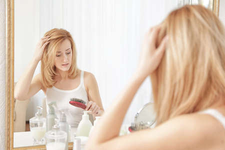 Young woman with hair loss problem in front of mirror at home