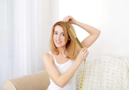 Hermosa joven midiendo la longitud del cabello mientras está sentado en el sofá en casa Foto de archivo