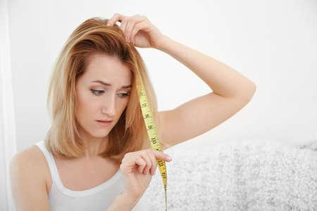 Hermosa joven midiendo la longitud del cabello en casa