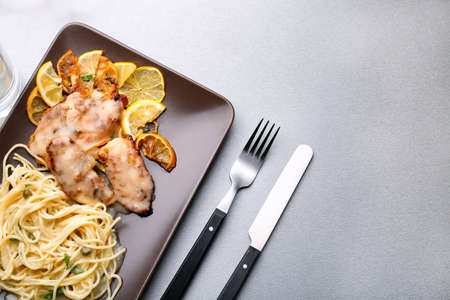 Plate with delicious Italian chicken piccata on table