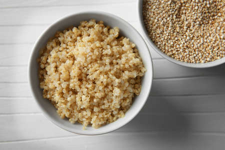 Top view of two white bowls with sprouted organic quinoa grains on white wooden background Zdjęcie Seryjne