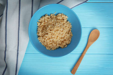 Top view of blue plate with sprouted organic white quinoa grains on wooden background