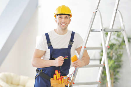 Young electrician standing near stepladder
