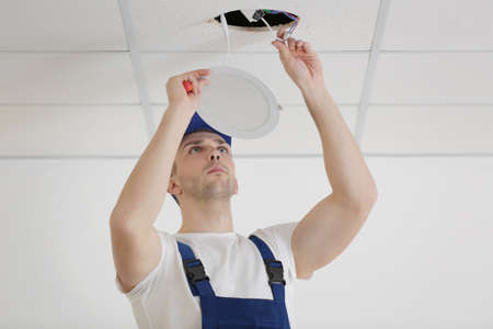 Electrician repairing ceiling light