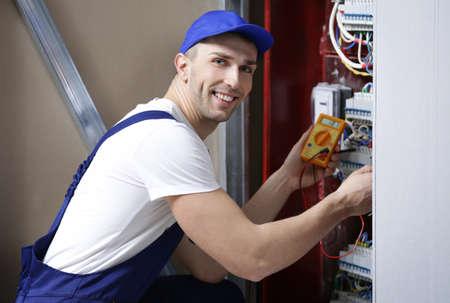 Electrician measuring voltage in distribution board
