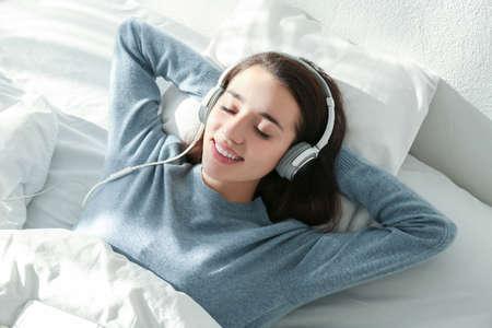 Jonge vrouw die aan muziek in hoofdtelefoons op bed luistert