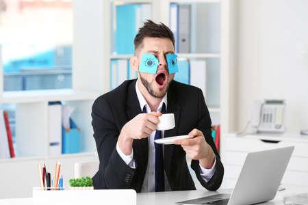 Jeune homme d'affaires avec de faux yeux peints sur des autocollants en papier bâillant au lieu de travail au bureau Banque d'images