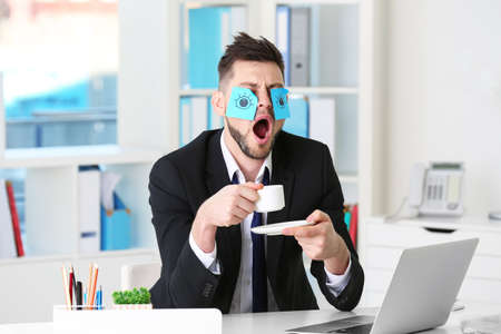Young business man with fake eyes painted on paper stickers yawning at workplace in office