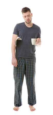 Young sleepy man in pajamas holding cup and newspaper on white background