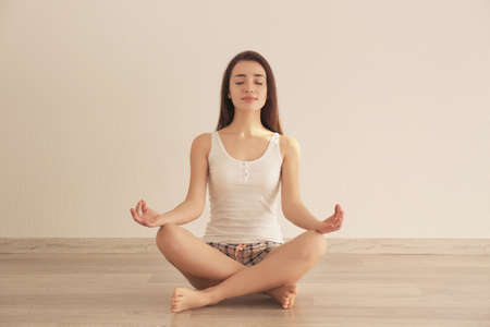 Young woman practicing yoga on floor