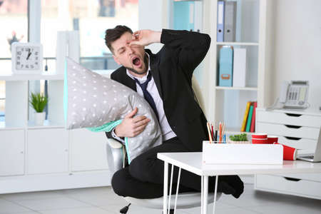 Tired business man with pillow on chair at workplace in office