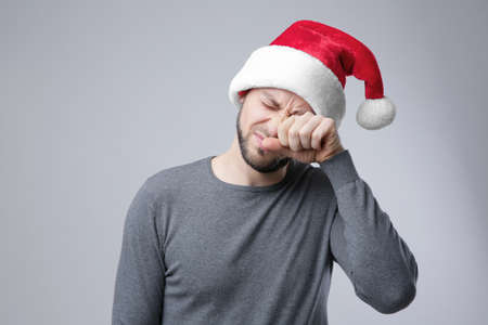 Sleepy guy in Xmas hat rubbing eyes on light background Stock Photo