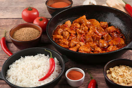 Frying pan with delicious chicken tikka masala and bowl with rice on wooden table