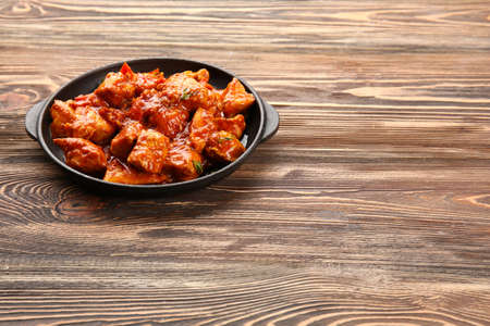 Frying pan with delicious chicken tikka masala on wooden table