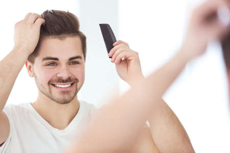 Handsome young man combing hair while standing in front of mirror Stock Photo