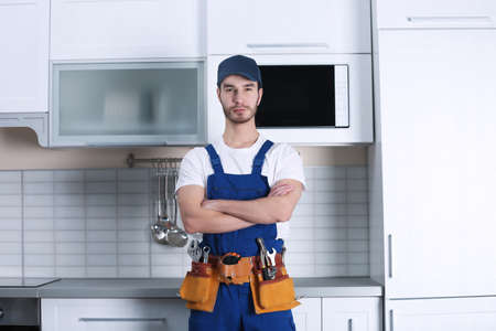 Handsome young worker in kitchen