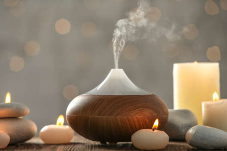 Aroma oil diffuser and candles on blurred background