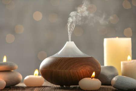 Diffusore di olio aromatico e candele su sfondo sfocato