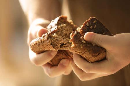 Man breaking off piece of bread, closeup Stock Photo