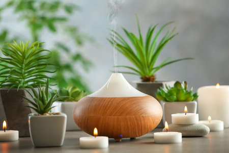 Aroma oil diffuser, candles and plants on table Фото со стока