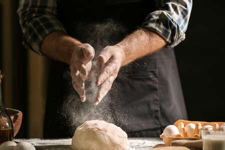 Man making dough in kitchen Foto de archivo