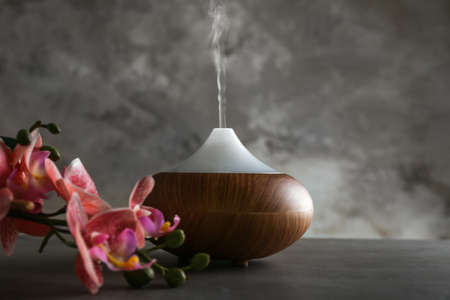 Aroma oil diffuser and orchid on table