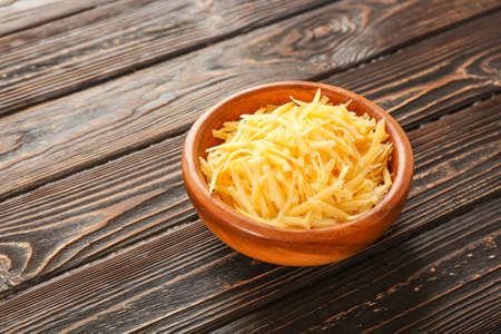 Bowl with grated cheese on wooden table