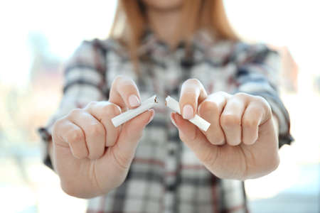Closeup view of woman breaking cigarette in hands