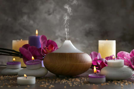 Aroma oil diffuser, candles and flowers on table