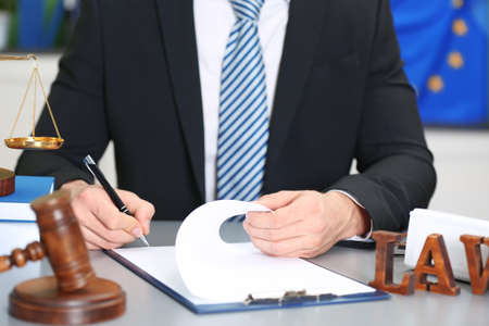 Male judge working with document and law accessories on table