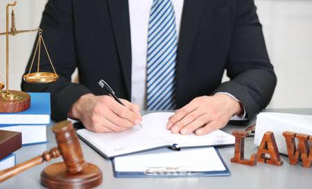 Juge mâle travaillant avec document et accessoires de la justice sur la table Banque d'images - 97475436