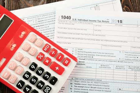 Calculator and individual income tax return form on table