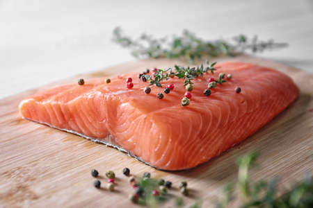 Peppered salmon fillet on wooden cutting board